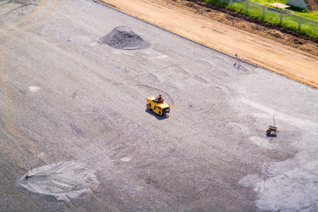 Asphalt roller rolls out gravel in the school stadium.