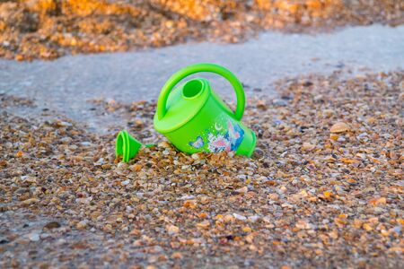 Childrens toy for watering flowers on the beach Stock Photo