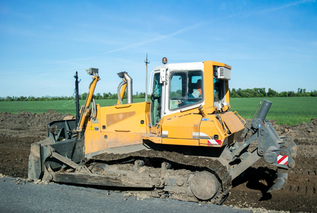 Crawler bulldozer at work to expand the roadway. Side view, Close
