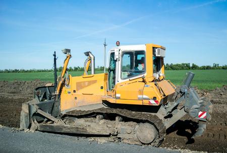 Raupen-Bulldozer bei der Arbeit, um die Fahrbahn zu erweitern. Seitenansicht, Schließen