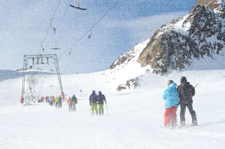 t ski: T bar ski lift pulling couple of skiers up the slope. Snowy winter in European Alps. Stock Photo