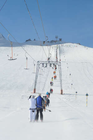 t ski: T bar ski lift pulling skiers up the slope. Wide ski slopes on left and right. Stock Photo