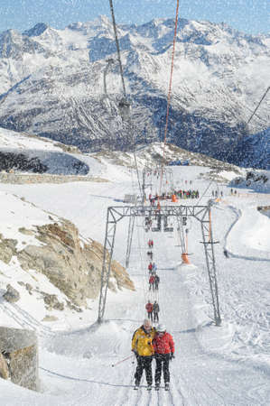 t ski: .T bar ski lift pulling skiers up the slope. Beautiful mountain landscape.. Snowy winter in European Alps.