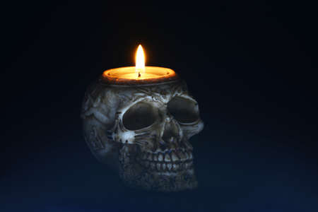 necromancy: creepy skull candle on black background - half turn