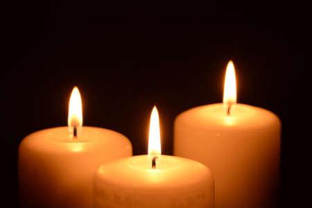 Drie kaarsen op een zwarte achtergrond