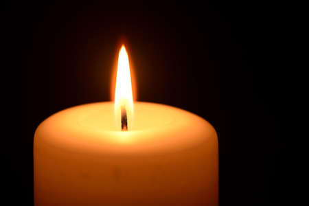 memorial candle: Burning candle on a black background Stock Photo