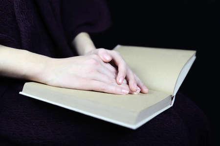closed book: female hands on a closed book