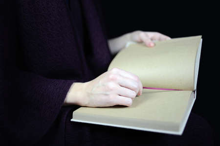 unfold: female hands holding an open book Stock Photo