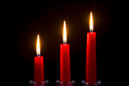 candleholder: Three red candles on a black background Stock Photo