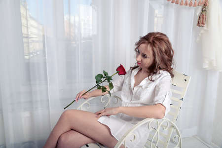waiting glance: woman with a rose sitting on a chair in front of the window