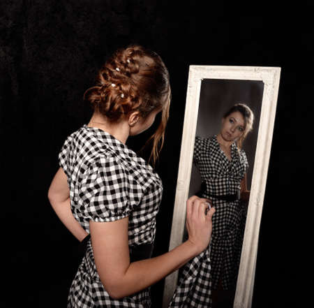 woman mirror: woman in a shirt looking in the mirror