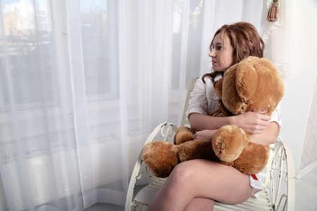 봉제 곰이 창문 근처에 의자에 앉아 여자