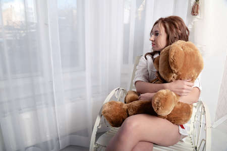 waiting glance: woman with a plush bear sitting on a chair near the window Stock Photo