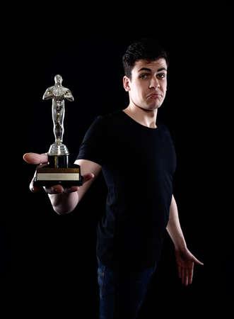 oscar: young man holding fake oscar award Stock Photo