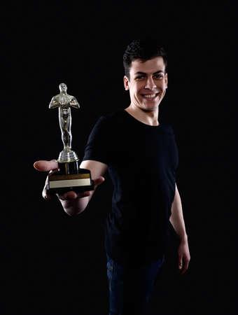 young man holding fake oscar award Stock Photo - 58031554