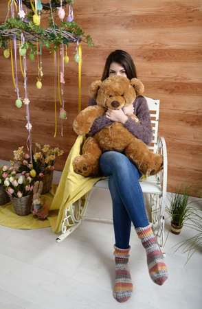 angry teddy: angry girl with a plush bear sitting on a chair