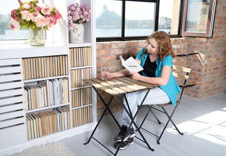 창 근처 의자에 책을 읽고 여자 스톡 콘텐츠