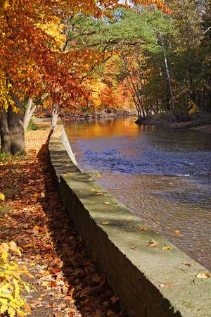 retaining: Fall scene river, retaining stone wall, glorious trees, splendid colors. Stock Photo