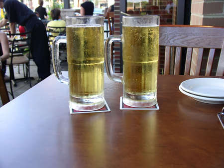 Two mugs of beer served at outdoor restaurant. photo