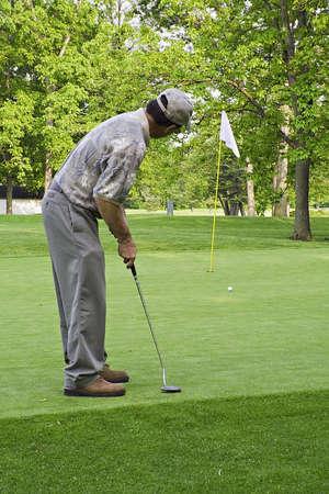 Man putting a golf ball toward the hole.