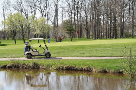 Golf Cart by pond Stock Photo