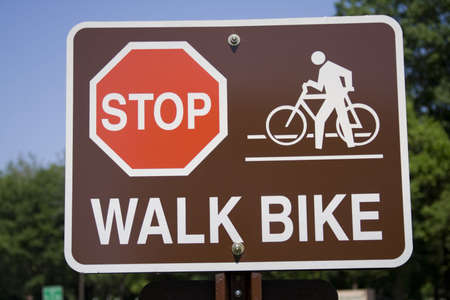 Sign ordering bikers to Stop and Walk Bike - not sharpened.