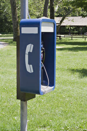 Outdoor telephone booth payphone in a public park. Banco de Imagens