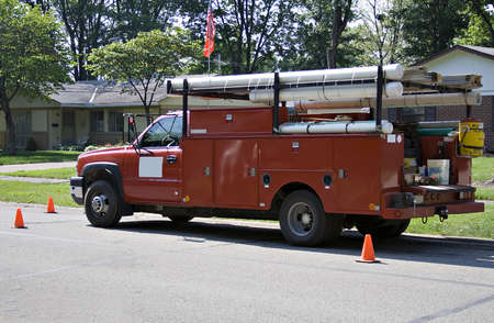 Red work truck in suburban neighborhood working on a construction project. Stock Photo