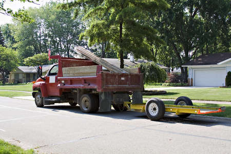 truckload: Red construction dump truck  carrying lumber with trailer working in a surburban neighborhood. Stock Photo