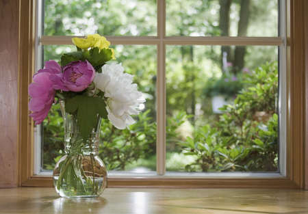 Window looking out to a beautiful Spring Summer view.  Floral Arrangement of peonies and other flowers. photo