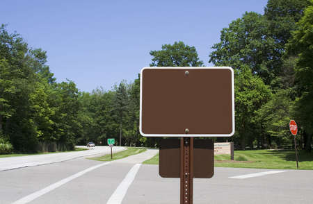 A blank sign posted along roadway in a park.  Add your own message photo