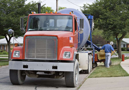 residential neighborhood: A big red cement truck working in a residential neighborhood.