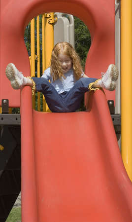 Small Red Haired little girl playing on a slide in playground on a warm June day. Stock Photo - 430925