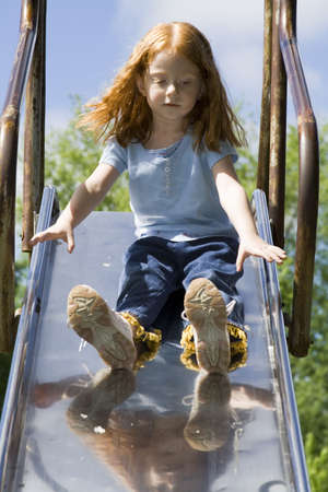 Small Red-haired girl on the large metal slide for the first time. Stock Photo - 430924
