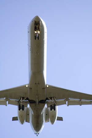 arrive: Underside of jet - very close range.  Landing gear down and approaching runway.