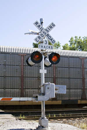 Train crossing - gales are down and lights are flashing - clear summer day.