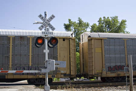 Train crossing - gates are down and lights are flashing - clear summer day. Banco de Imagens