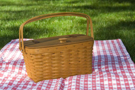 was: Not sharpened. Wooden woven picnic basket with was handmade in Ohio, sitting on red and white checked table cloth.