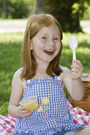 Small pre-school girl eating a container of applesauce while picnicing in the park. Stock Photo - 439495