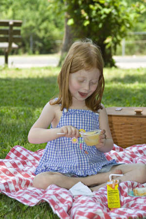 Small red-haired girl eating a cup of applesauce outdoors in a park - picnic setting. Stock Photo - 439494