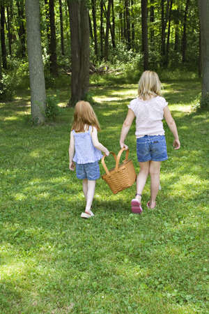 shady: Two young girls carrying a picnic basket in a shady park.