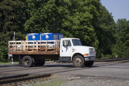 Truck transporting hazardous chemicals crossing a railroad track. Imagens