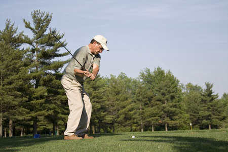 midst: 53-year old man in the midst of a powerful golf swing. Stock Photo