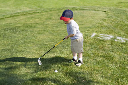 two year old: Two year old boy practicing golf swing. Stock Photo