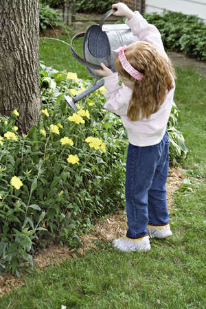 Small red-haired girl watering the summer flowers. Stock Photo - 439469
