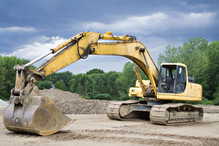 grader: Large Yellow Back Hoe at Construction site.  Storm brewing.