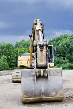 A Backhoe parked at the construction scene - storm brewing - cloudy dramatic sky. photo