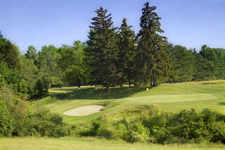 A scenic view of a  golf course - looking down over sand trap and distant green.