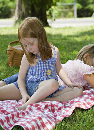 Small redhead girl examining a mosquito bite on her ankle.  Relaxing after picnic in park. Stock Photo - 450122