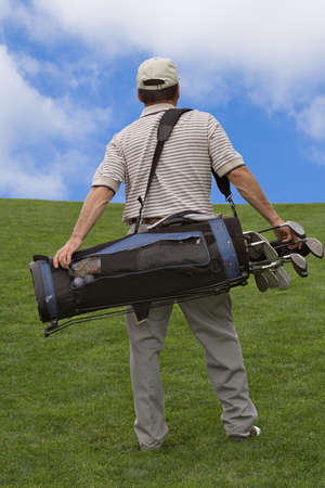 Man walking up hill carry bag of golf clubs.